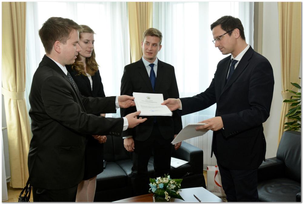 Gulyás Gergely miniszter átveszi a folyamodványt Hetzmann Róbert elnöktől – a küldöttség további tagjai dr. Juhász Kitti és Kassay Gergő